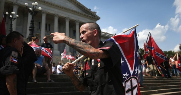 The small group was quickly dispersed by police officers fearing tensions between KKK members and local protesters would escalate into violence